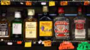 Store shelves of alcohol bottles including Buckfast and Smirnoff. Quality image.