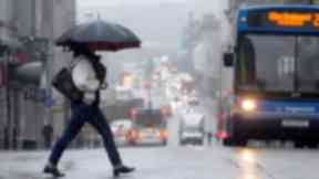 General view of heavy rain in Glasgow city centre woman with umbrella. Quality image.