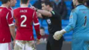 Referee Euan Norris (centre) waves away protests from Aberdeen players before booking Niall McGinn for simulation