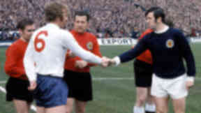 Scotland captain John Greig (right) exchanges handshakes with England counterpart Bobby Moore as referee Schulenburg prepares to get the match underway.