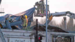 Firefighters at the Clutha bar in Stockwell Street, Glasgow, after police helicopter crashed into the roof of the building