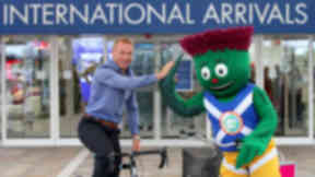 Sir Chris Hoy high fives Clyde the 2014 Games Mascot at the new international arrivals are at Glasgow Airport.
