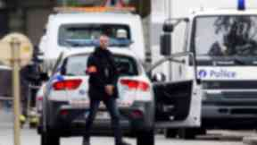 A plainclothes police officer patrols near a Brussels apartment building on June 17.