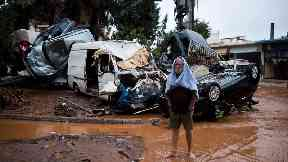 A barefoot man stands in front of a pile of vehicles after flash flooding near Athens.