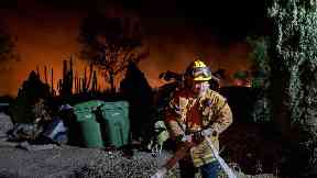 Firefighter works to defend homes from an approaching wildfire in Los Angeles, California.