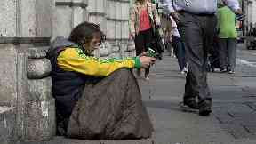 Members of the public walk past a homeless man begging in central London.