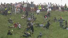 Competitors take part in the annual cheese rolling competition at Cooper's Hill in Brockworth, Gloucestershire.