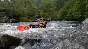 Kayaker paddling on the River Tummel, Clunie Dam.