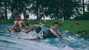 Boys going down homemade waterslide in a field, image from Unsplash