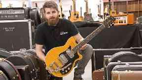 Auctioneer Luke Hobbs with George Harrison's Maton guitar.
