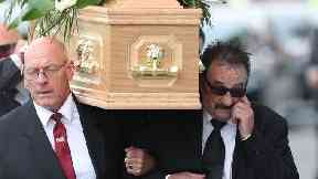 Paul Elliott (right) carries the coffin of his brother Barry into his funeral.
