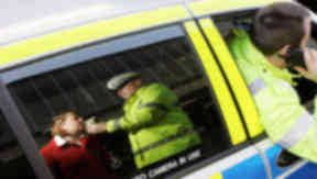 Quality shot of police officer giving drink drive suspect a breath test.