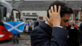 Ed Miliband Labour leader looking annoyed, upset, defeat, with saltire in the background. Quality image.
