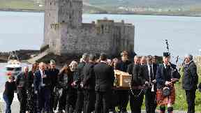Funeral: A piper led a procession to the shore after Eilidh was flown home.