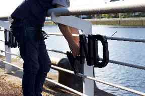 Helping hand: Ahmad threads the letters onto the railings.