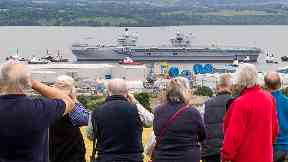 Crowds: People watch carrier make her way down the Firth of Forth.