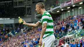 Leigh Griffiths picks up a bottle of Buckfast that was thrown in his direction.