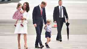 The royal family walk on the tarmac after leaving the plane.