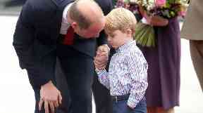 Prince George holds his father's hand.