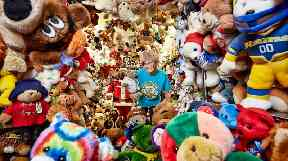 Jackie Miley is almost hidden among her collection of teddy bears.