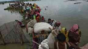 Rohingya wade through water as they flee their homes.