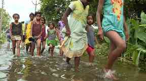 Children paddle through floodwaters in India.