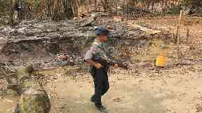 A Myanmar security officer walks past burned Rohingya houses.