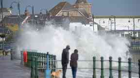 Dog walkers in Penzance watched as high waves crashed against the harbour.