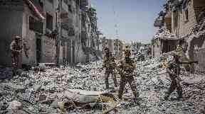 SDF soldiers move through debris in the Al Dariya neighborhood in western Raqqa