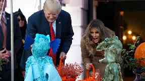 President Trump and Melania greet children in Halloween costumes.