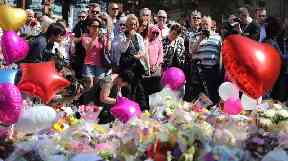 People look at tributes in St Ann's Square, Manchester, before a minute's silence to remember the victims of the terror attack in the city.