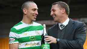 Captain Scott Brown and Brendan Rodgers celebrate the 63-game unbeaten run with a bottle of champagne.