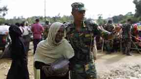 A soldier in Bangladesh distributes aid to a Rohingya refugee.