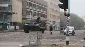 Soldiers and an armoured vehicle patrol on a street in Zimbabwean capital Harare.