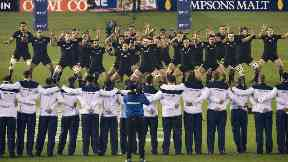 The Scotland players watch on as the New Zealand players perform the Haka.