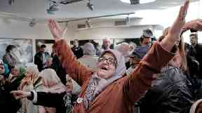 A Bosnian woman raises her arms in celebration following the verdict.