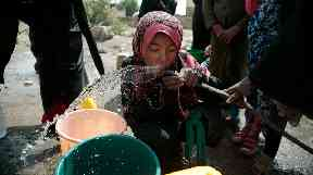 A girl drinks water from a well that was alleged to be contaminated with the bacterium Vibrio cholera.