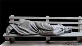Statue: Homeless Jesus lying on a bench.