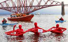 Swim: Three men dressed as the Fourth Bridge for the chilly charity challenge.