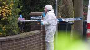 Forensic teams examine the Stockport property where a body was found.