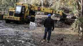 A bulldozer clears the debris in Montecito, Santa Barbara.