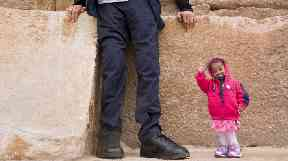 Jyoti Amage stands next to the legs of the world's tallest man.