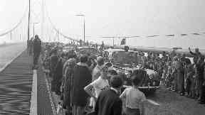 Opening: The Queen's car passing a crowd on the bridge.