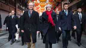 Prime Minister Theresa May and her husband Philip walk through a market after visiting the Yu Yuan Temple Garden in Shanghai.