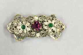 This brooch contains the three colours of the suffragette movement: green for hope, purple for dignity, and white - here silver - for purity.