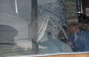 Newspaper: One worker in a bus using a Daily Mirror to hide his face.