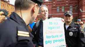 Gay rights campaigner Peter Tatchell is questioned and led away by Russian authorities.