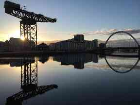 Glasgow's Finnieston Crane and the Squinty Bridge reflected in a calm River Clyde.