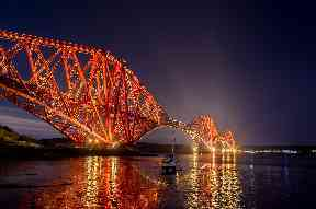 A boat is perfectly framed within the Forth Road Bridge and its reflection.