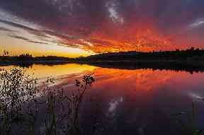 The Loch of Lintrathen by Kirriemuir reflects an atmospheric sunset sky.